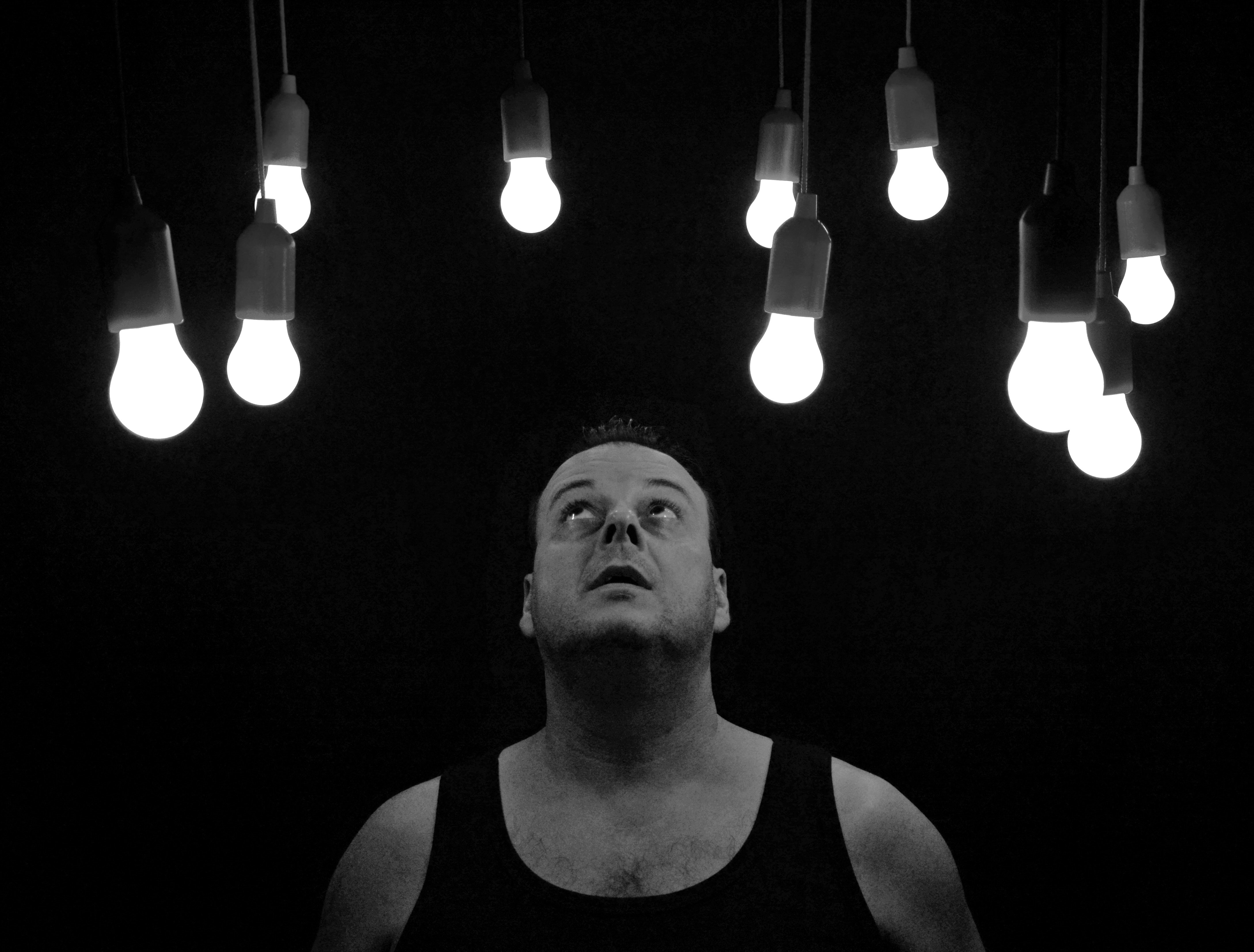 man looking at light bulbs