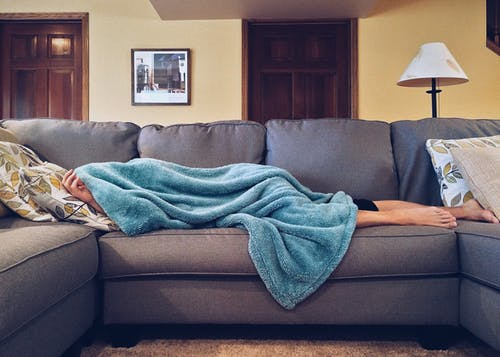 person laying on couch covered by a blanket